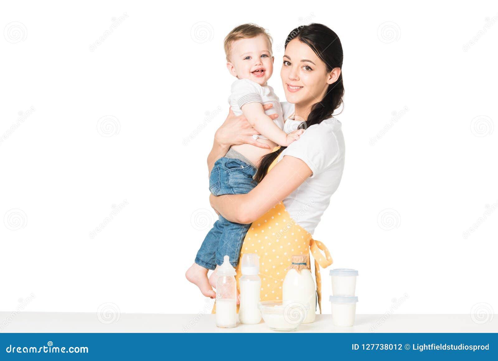 Den unga modern i förklädeinnehav behandla som ett barn pojken på tabellen med barnmat