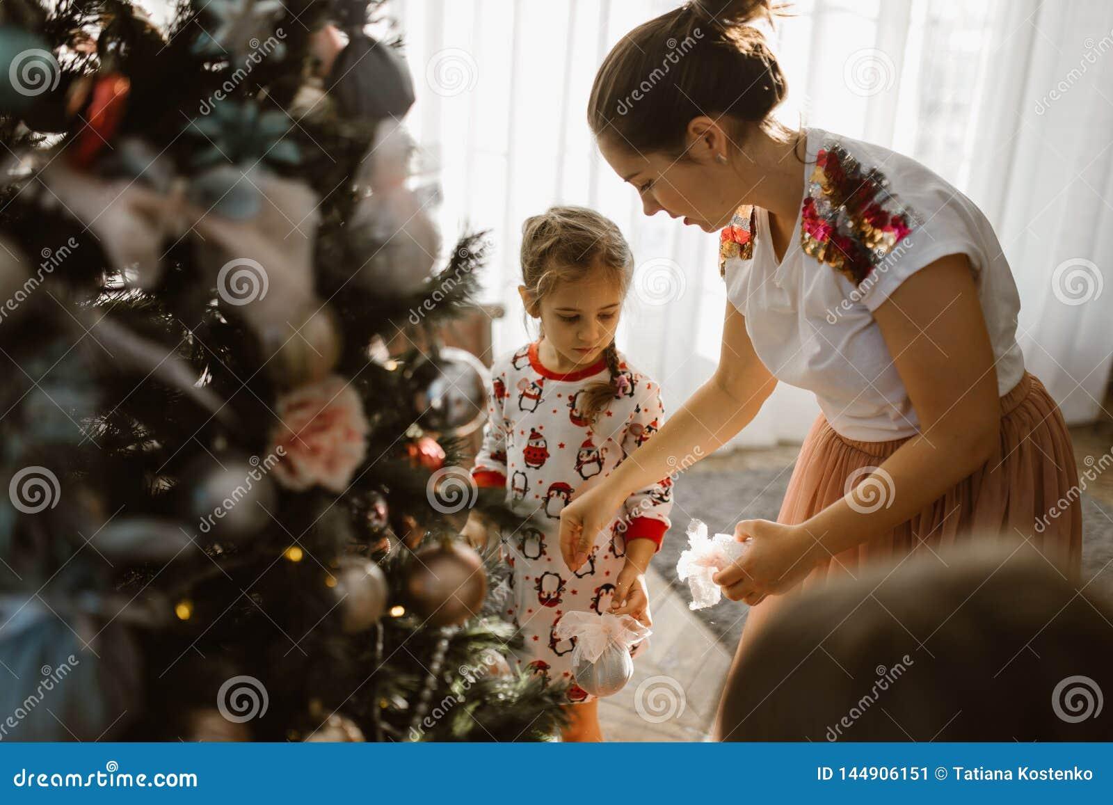 Den unga modern med två lilla döttrar i pyjamas dekorerar nytt års träd i det hemtrevliga rummet med med det stora ljusa fön