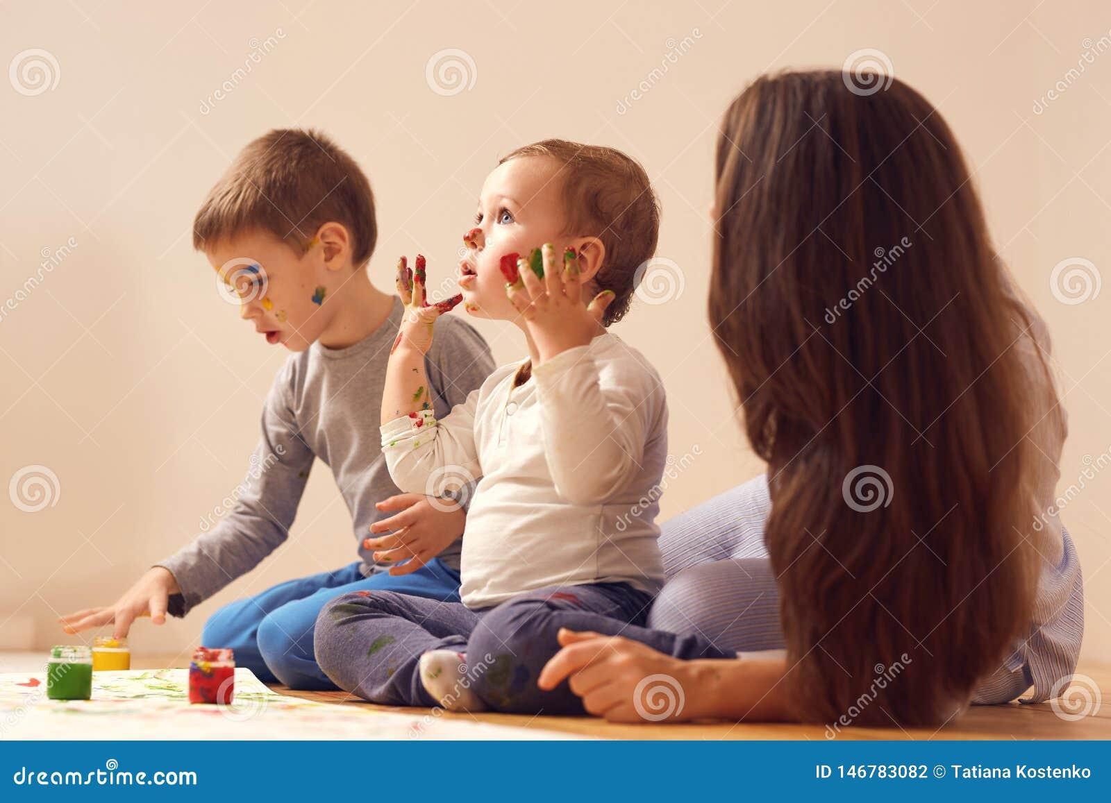 Den unga modern och hennes tv? ikl?dda hem- kl?der f?r sm? s?ner sitter p? tr?golvet i rummet och m?la
