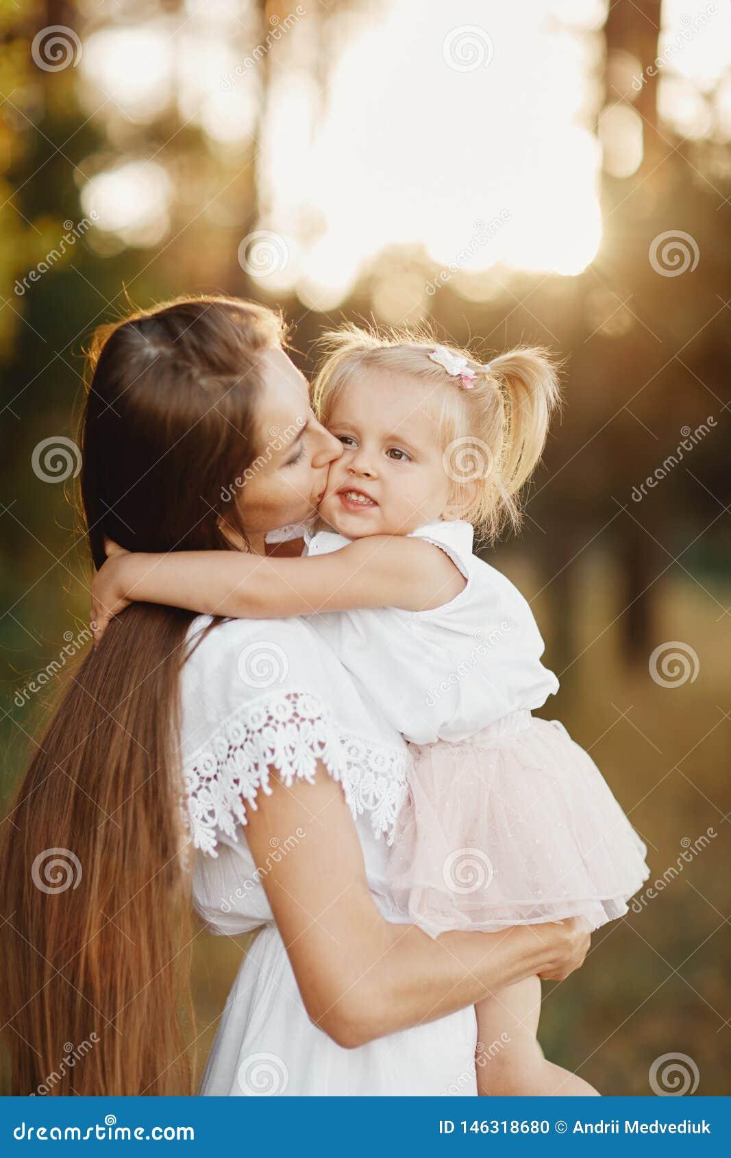 Den unga modern som tar omsorg av hennes litet, behandla som ett barn flickan mamma och hennes dotter utomhus ?lska f?r familj Fo
