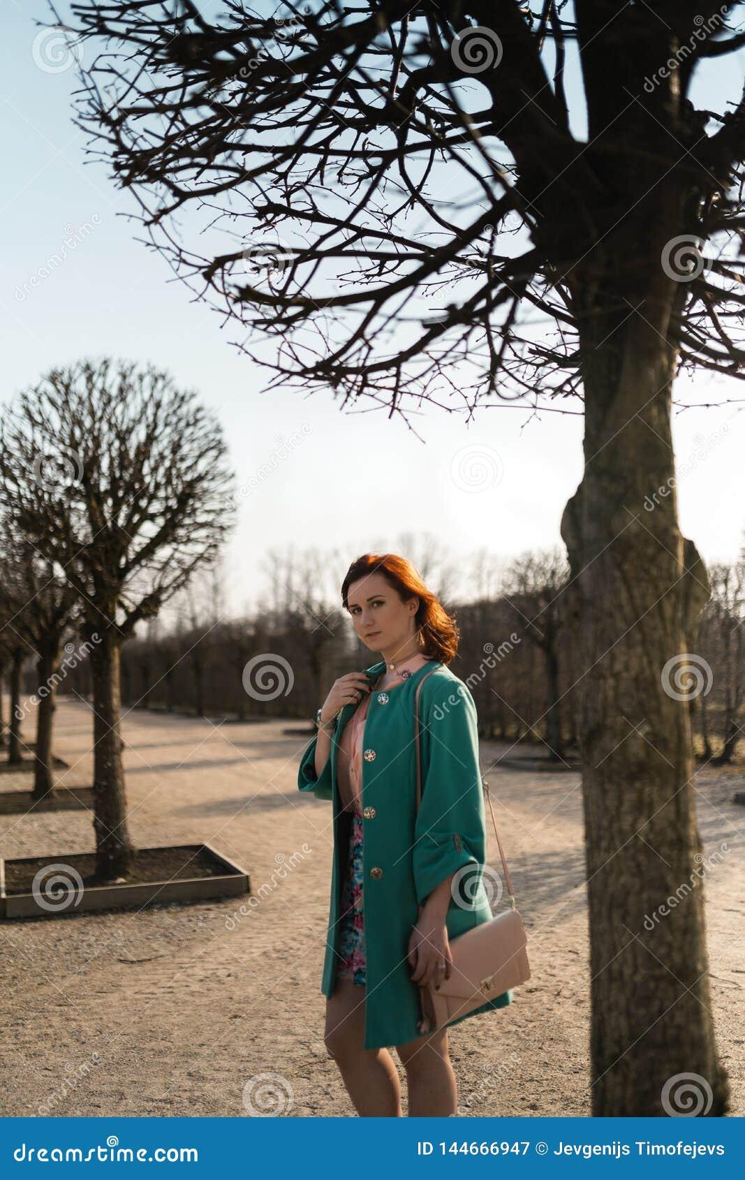Den unga modevänkvinnan som waling i, parkerar det bärande livliga gröna omslaget och en färgrik kjol