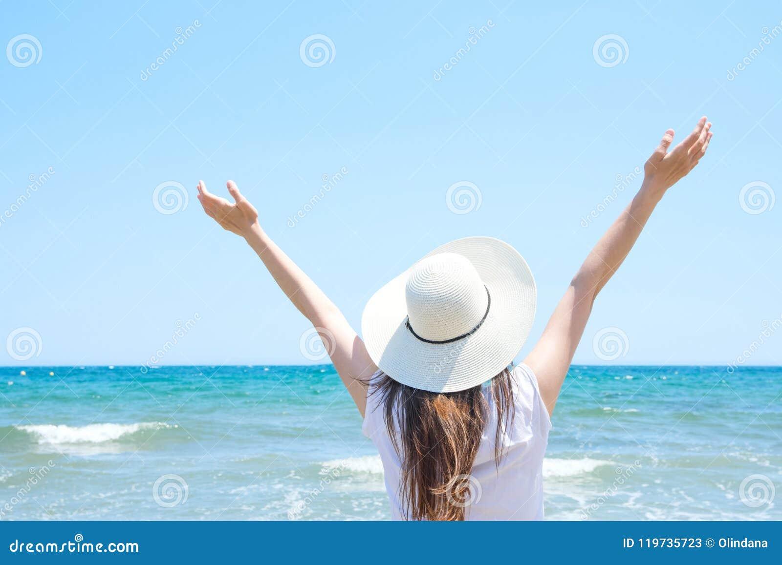 Den unga nätta Caucasian kvinnan med långt kastanjebrunt hår i hatthänder lyft upp i luftställningarna på stranden ser turkoshave