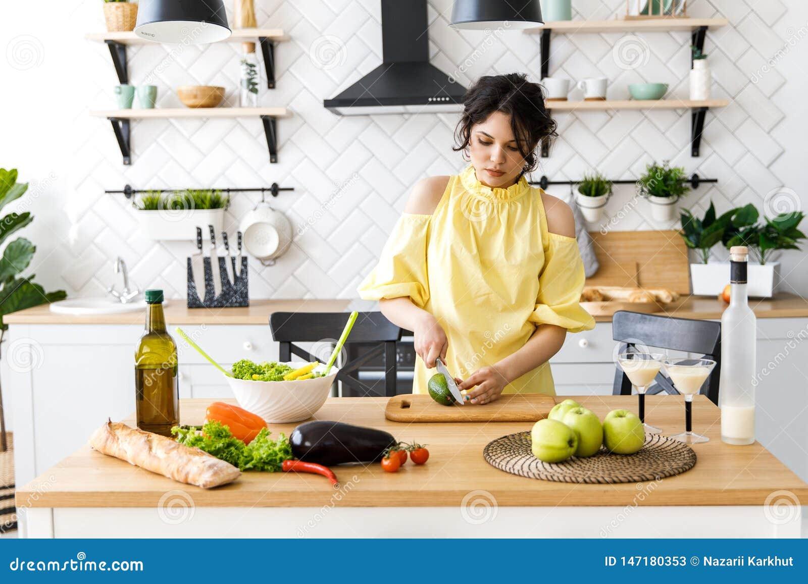 Den unga nätta kvinnan klipper en avokado på ett träsalladbräde matlagning Förberedelse av sallad för ny grönsak