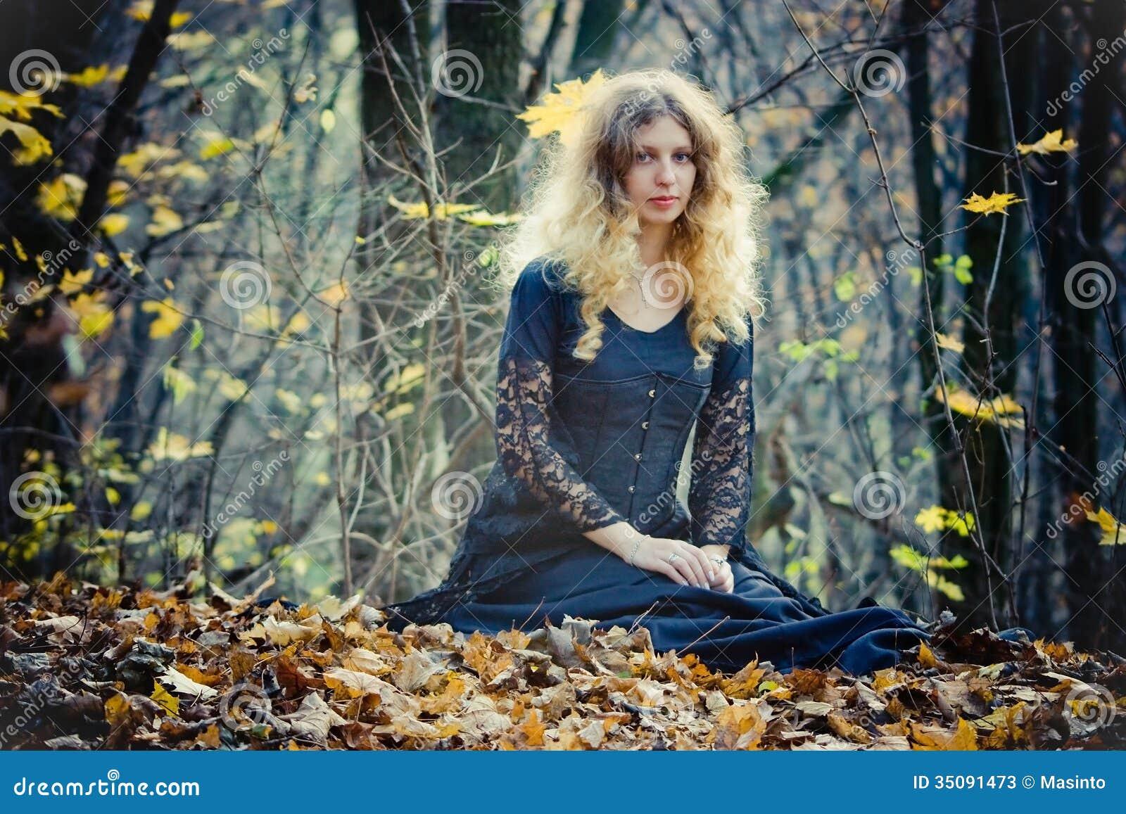 Den unga nätta kvinnan sitter i trät