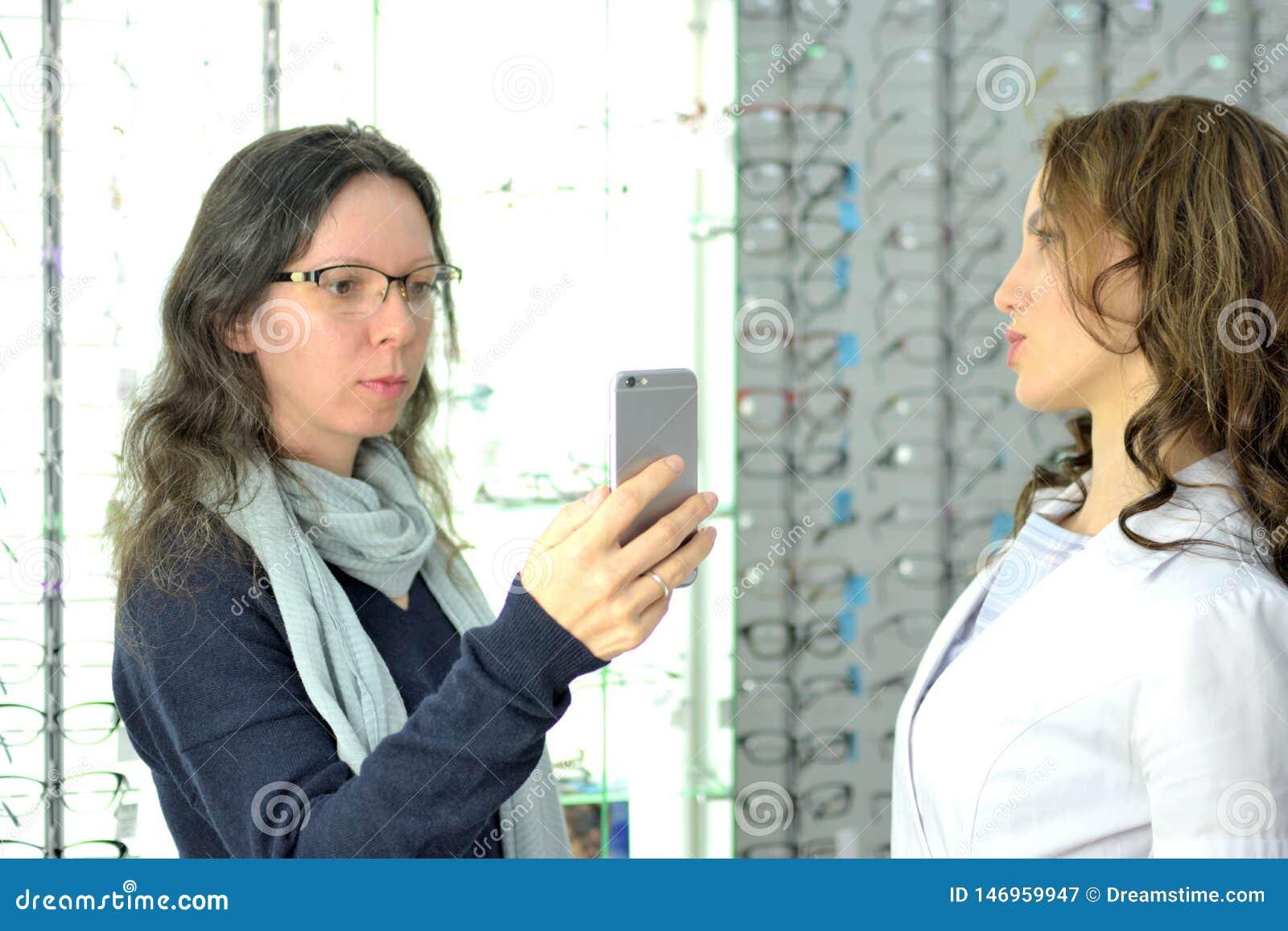 Den unga n?tta kvinnan f?rs?ker ?gonexponeringsglas p? en eyewear shoppar p? med hj?lp av shoppar assistenten och aktier i social
