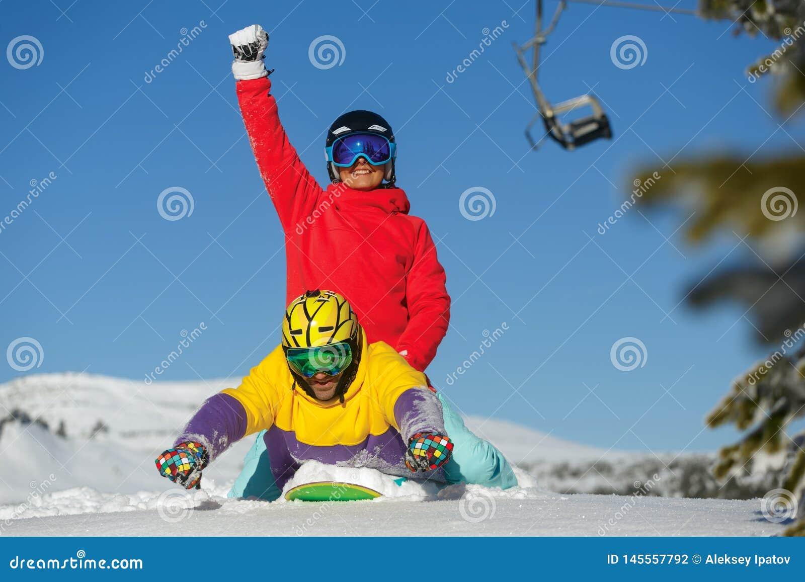 Den unga pojken och flickan har gyckel på vintern skidar semesterorten