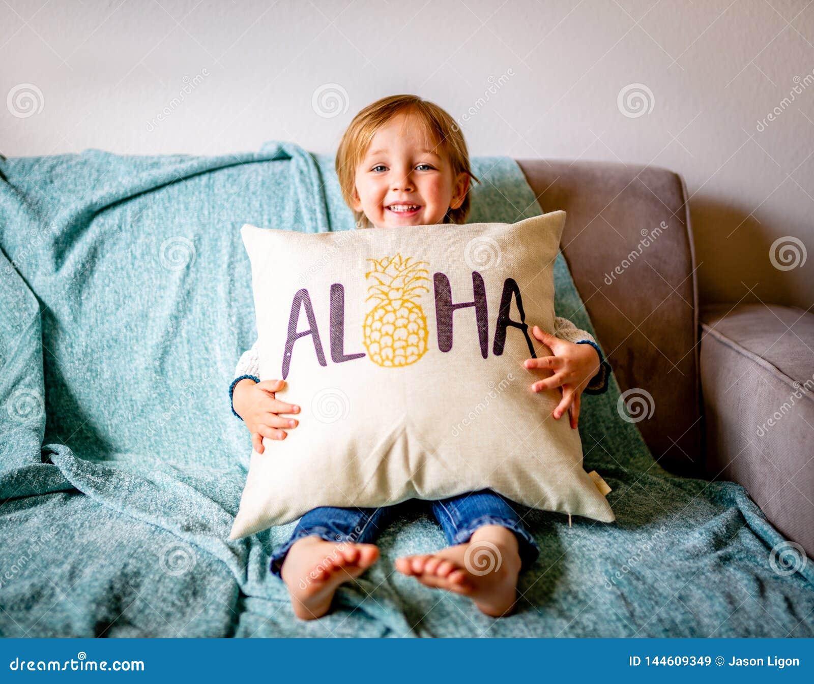 Den unga pojken sitter på soffan