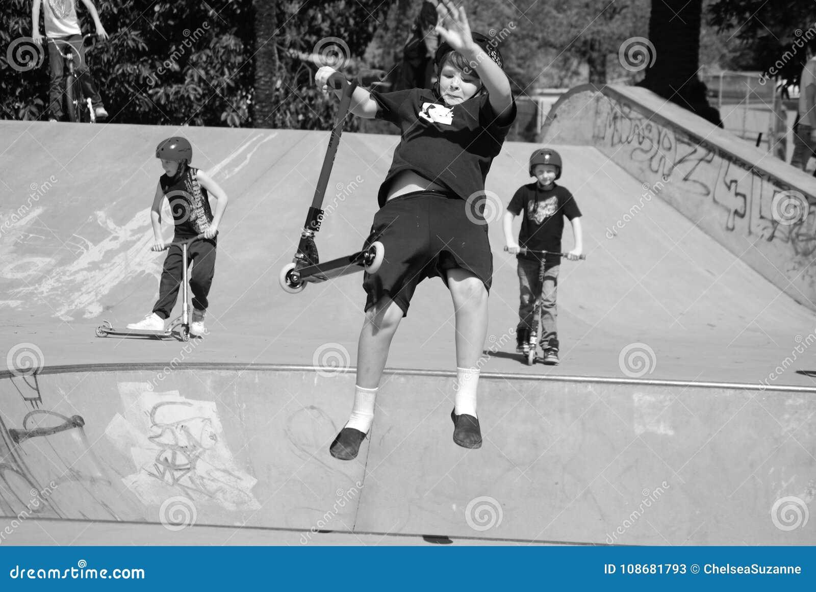 Den unga pojken, ungar parkerar, trick som rider sparkcykeln som högt hoppar i luft