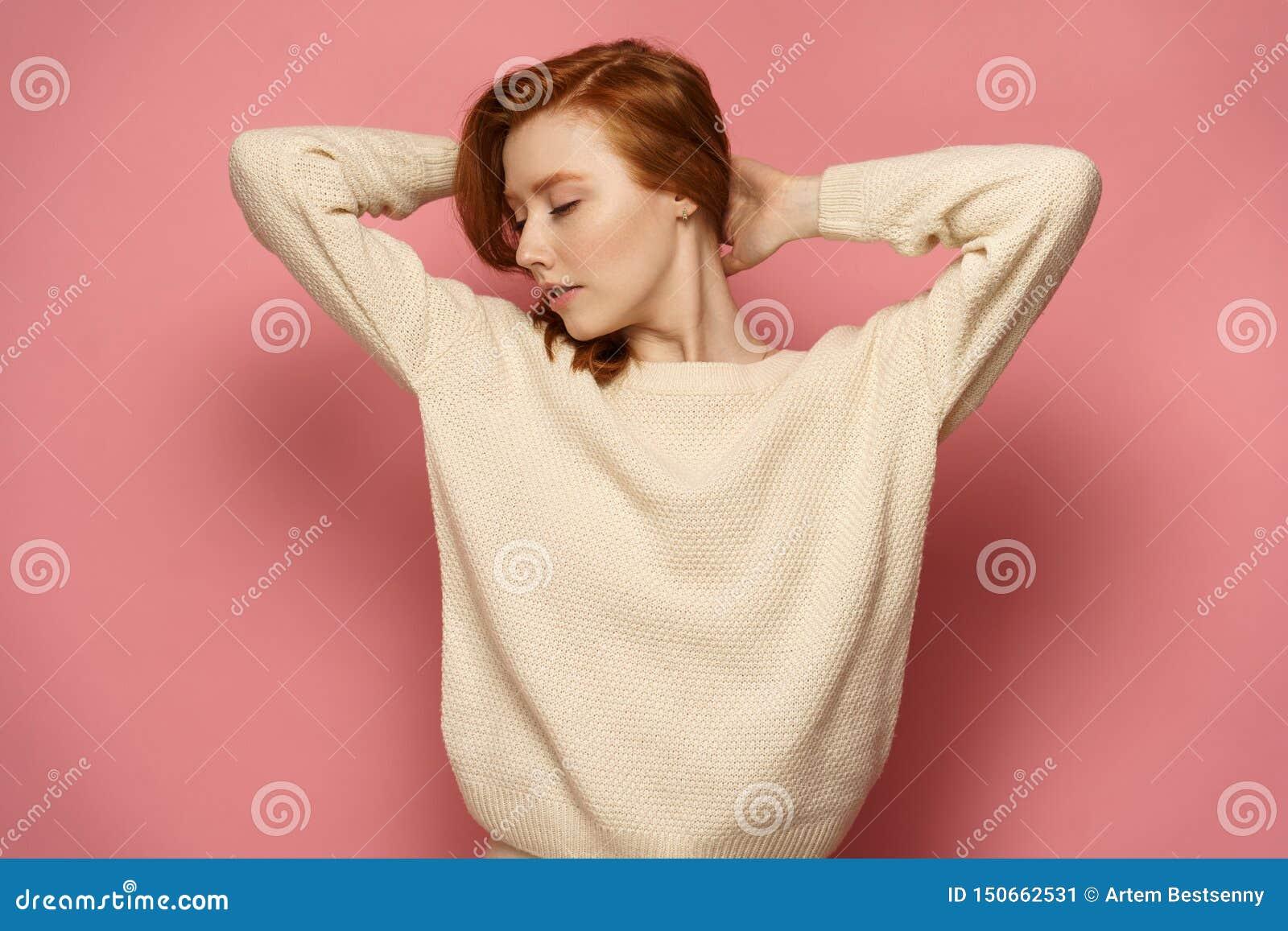 Den unga rödhårig manflickan med stängda ögon rymmer hennes hår som ner håller hennes huvud