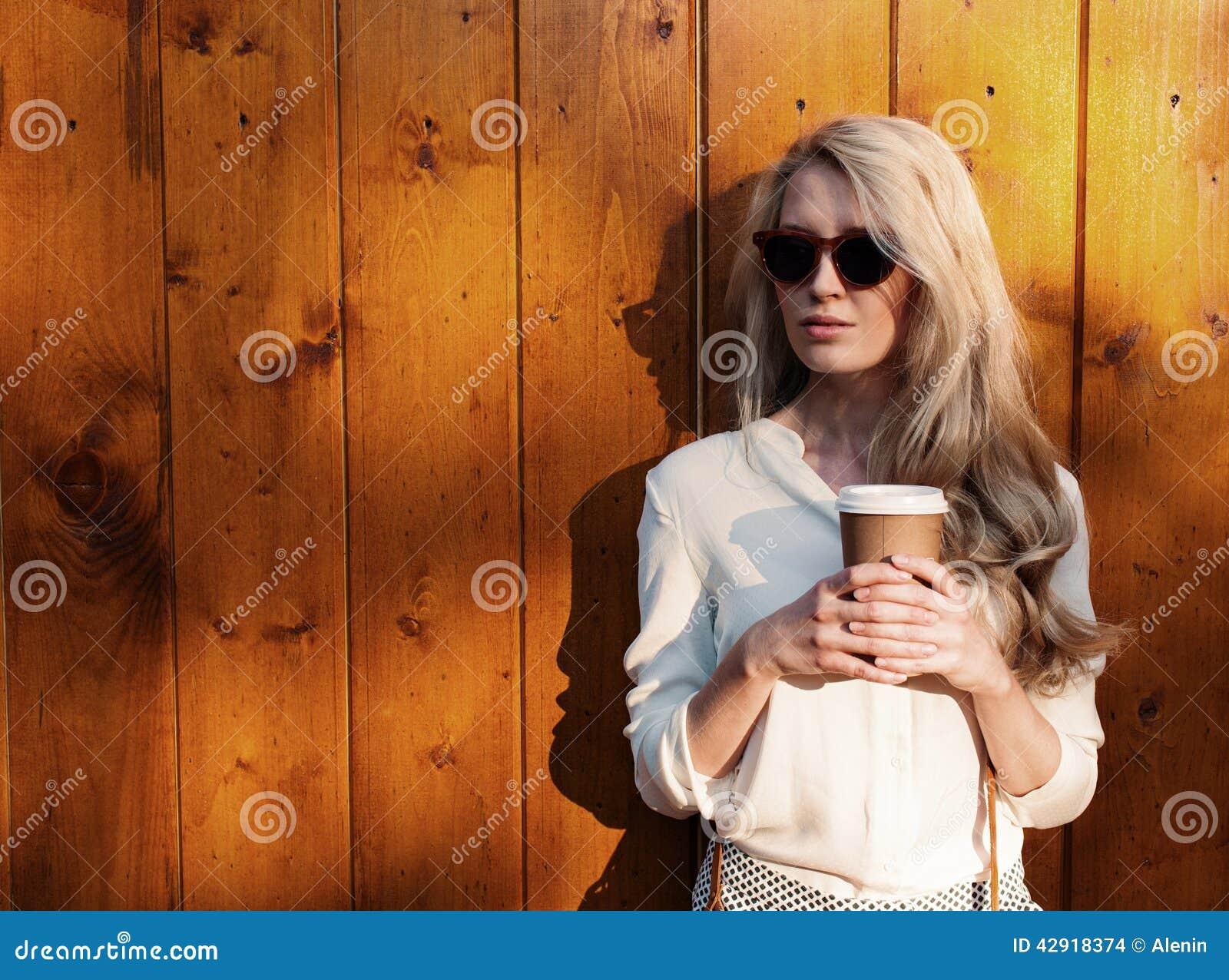Den unga sexiga blonda flickan med långt hår i solglasögon som rymmer en kopp kaffe, har mjukt solljus för rolig afton, varmt som