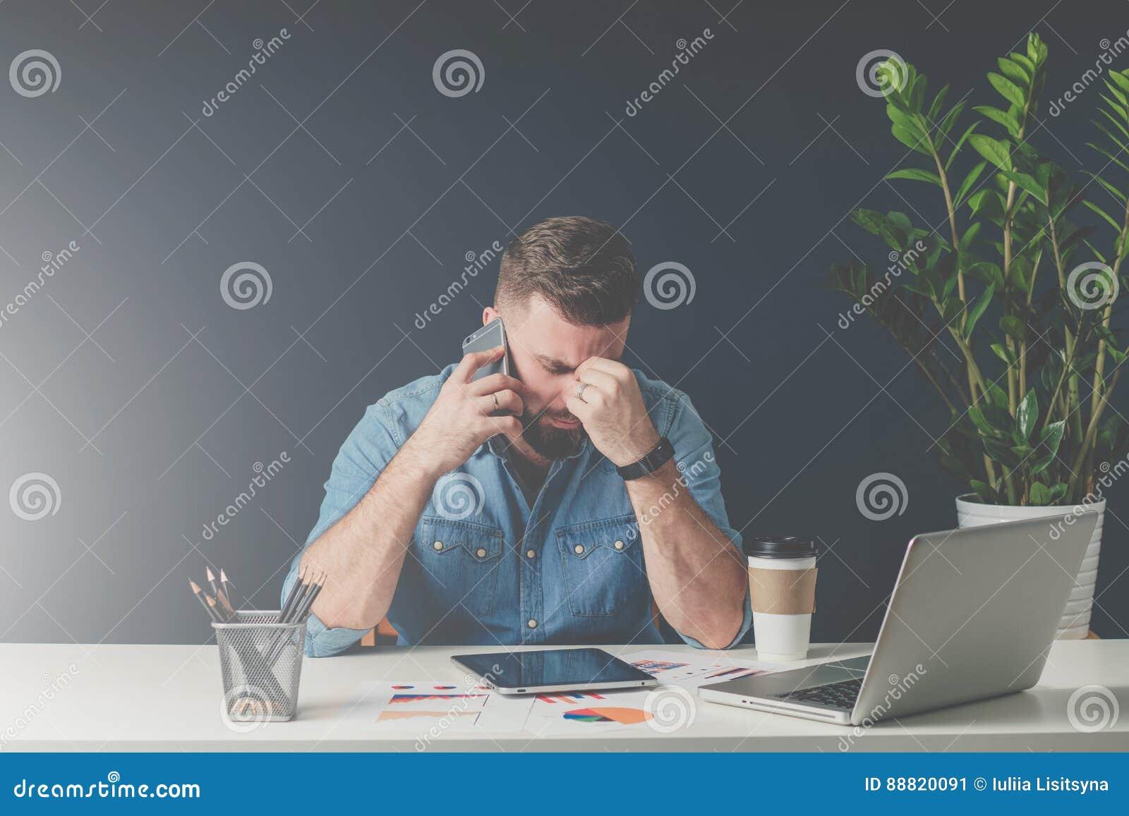 Den unga skäggiga ledsna affärsmannen sitter på tabellen som täcker hans framsida med hans hand och talar på mobiltelefonen
