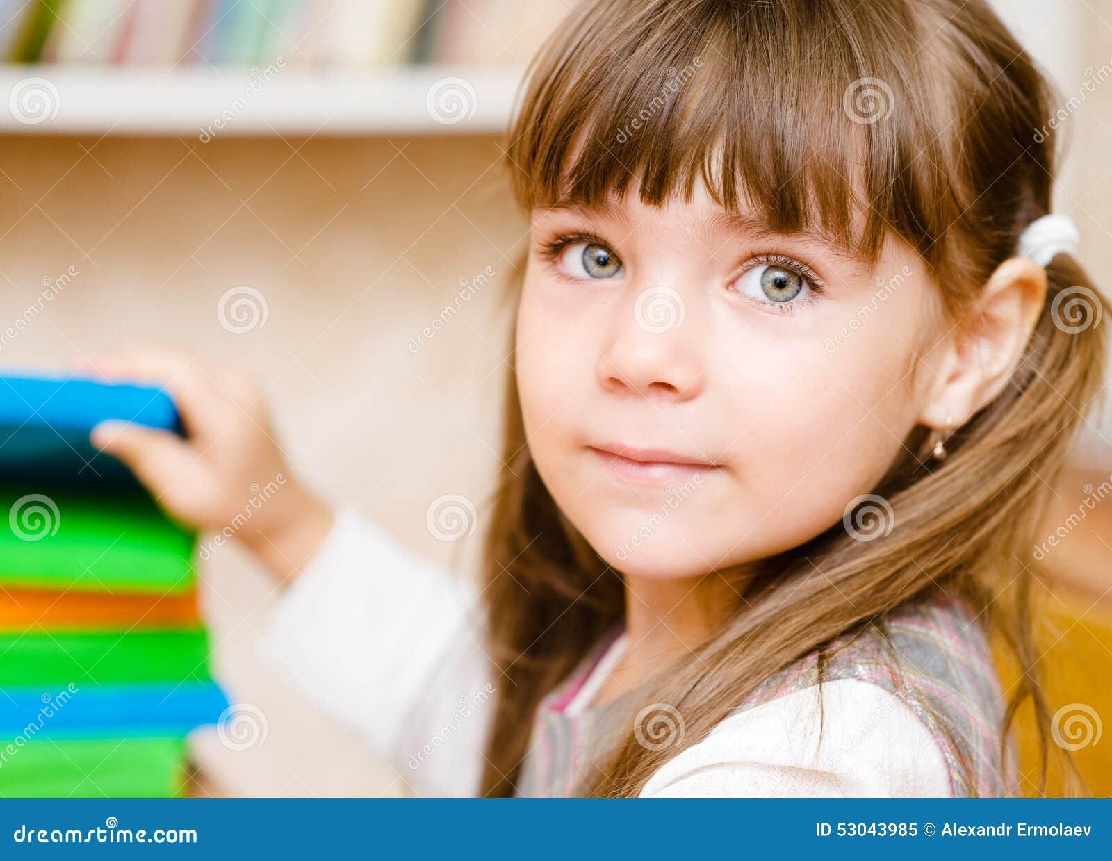 Den unga skolflickan tar en bok