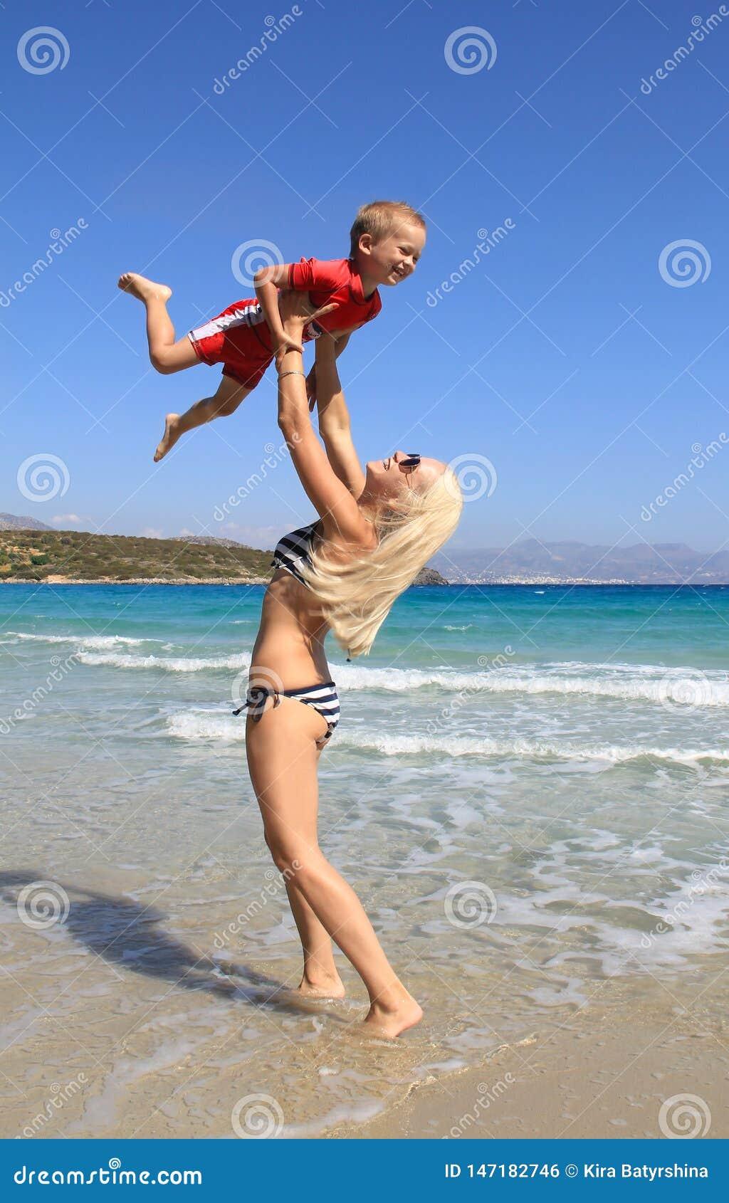 Den unga slanka kvinnan kastar upp och fångar hennes lilla son på stranden vid det klara blåa havet Modern och hennes gulliga lil
