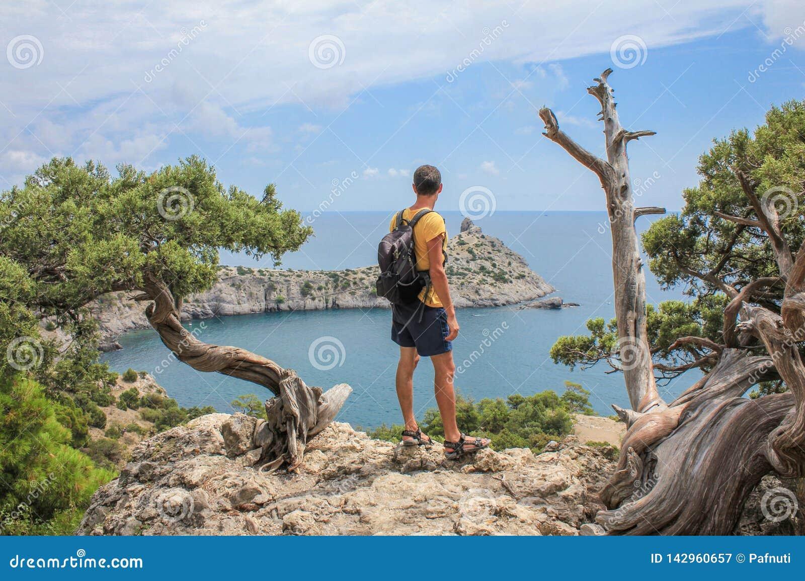 Den unga sportiga mannen med ryggsäcken som står på överkanten av, vaggar