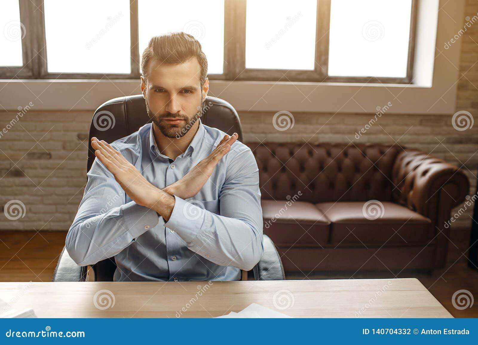 Den unga stiliga affärsmannen sitter på tabellen i hans eget kontor Han rymmer händer korsade i förbjudet tecken Ilsket och mycke