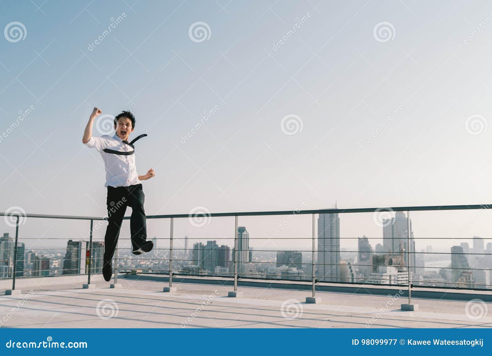 Den unga stiliga asiatiska affärsmanbanhoppningen firar att segra för framgång poserar på byggnadstaket Arbete, jobb eller framgå