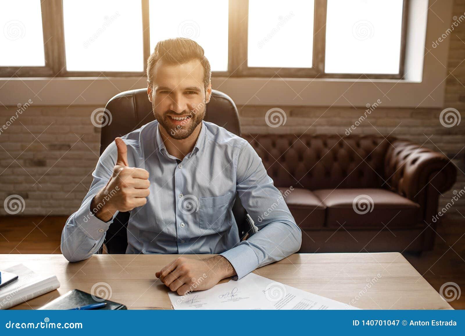 Den unga stiliga gladlynta affärsmannen sitter på tabellen och poserar i hans eget kontor Han rymmer den stora tummen upp och lee
