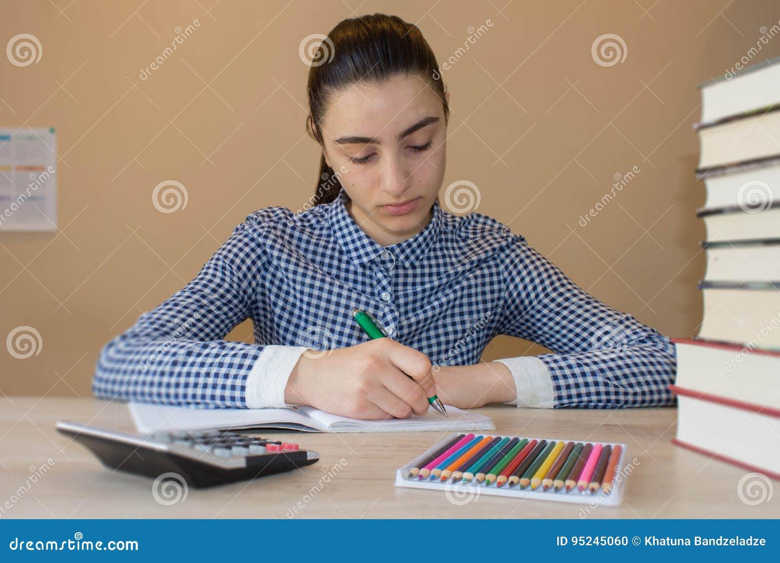 Den unga studenten med fundersamt uttryckssammanträde på ett skrivbord på något bokar Utbildningsbegrepp - den lilla studentflick