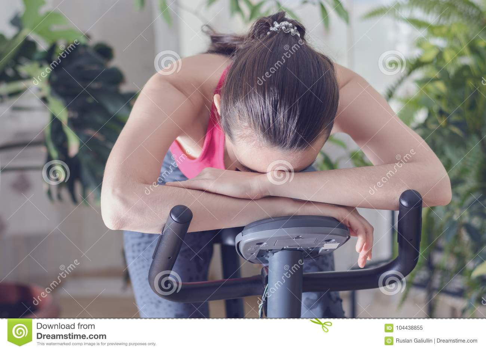 Den unga sunda passformkvinnan som utbildar på motionscykelen under, utarbetar evakuerad känsla och förvirrar hemma, fällt ned ha