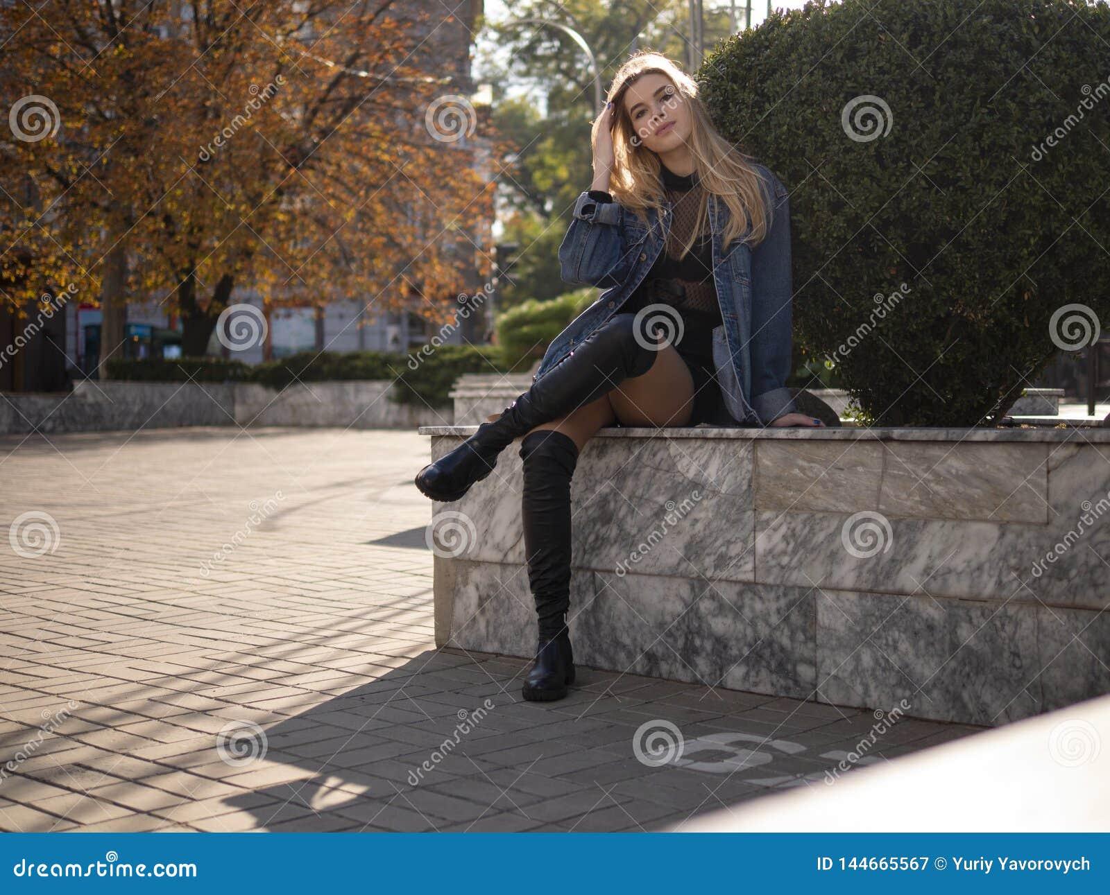 Den unga tonåriga flickan med brunn-ansat hår med härliga långa ben sitter på gatan med hennes korsade ben