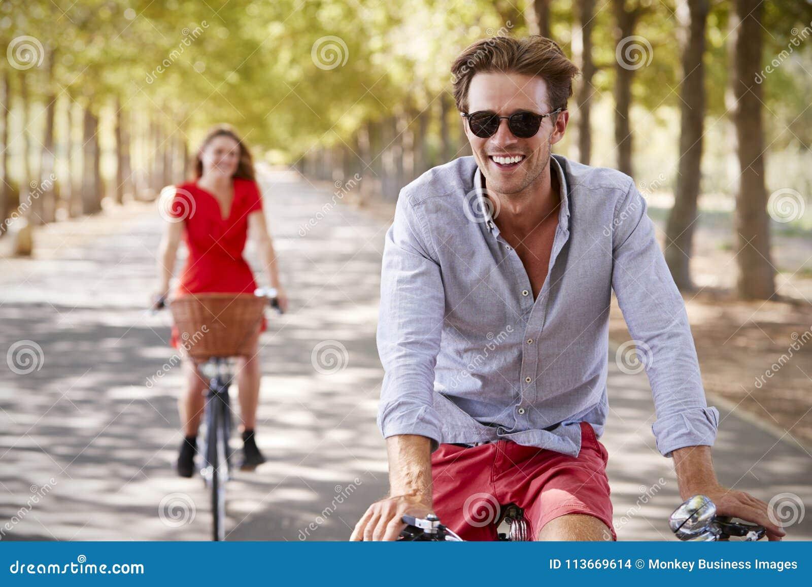 Den unga vita vuxna parridningen cyklar på en tyst solig väg