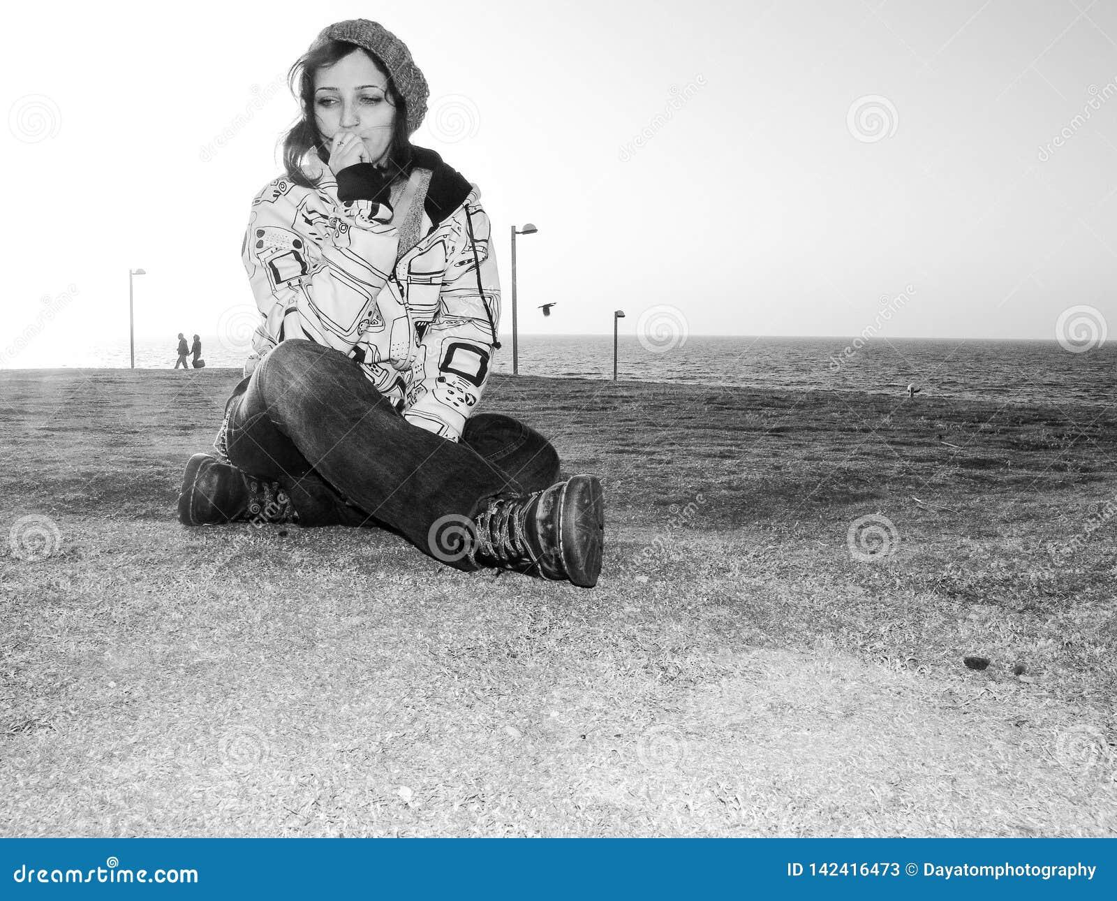 Den unga vuxna kvinnlign, bärande tillfällig dress, jeans, hatten och en hoodie, stads- stil som sitter på gräs på, parkerar med