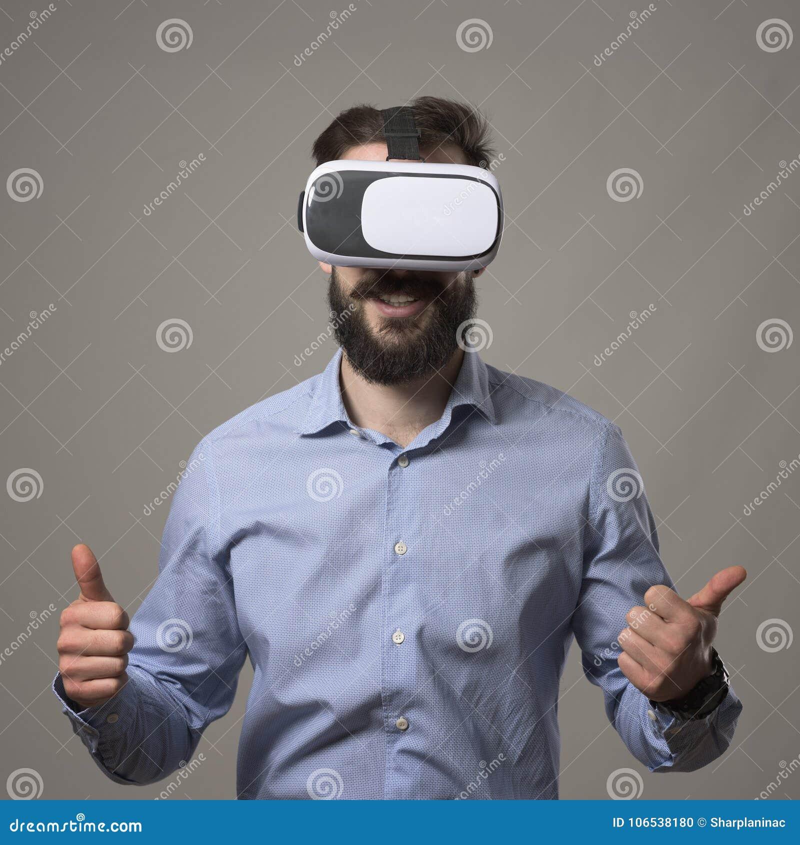 Den unga vuxna människan uppsökte den smarta tillfälliga hörlurar med mikrofon för vr för affärsmannen som bärande ler med tummar