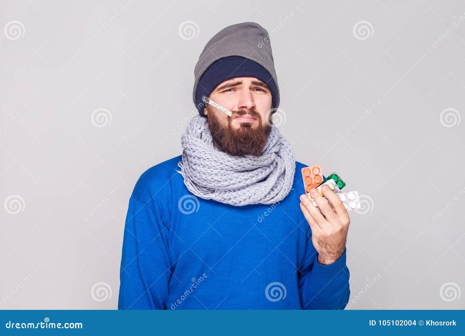 Den unga vuxna sjuka mannen har temperaturen som rymmer många preventivpillerar