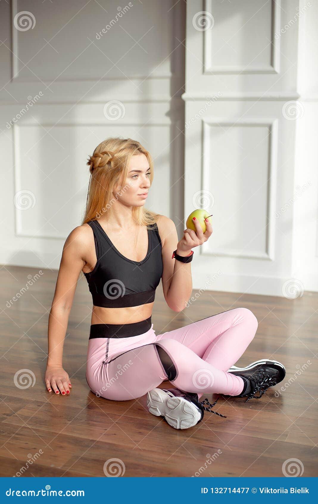 Den ungt slanka kvinnan med ett långt blont hår för idrotts- kropp som, är iklätt en rosa sportöverkant och damasker, sitter i et