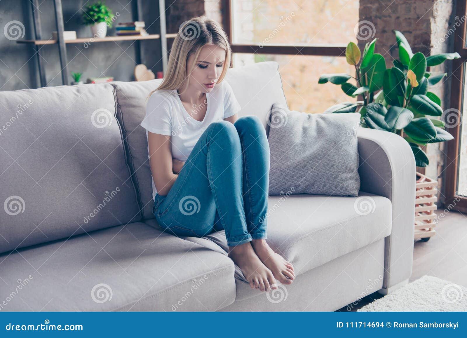 Den upprivna kvinnan har första tecken av pms Hon sitter på en soffa