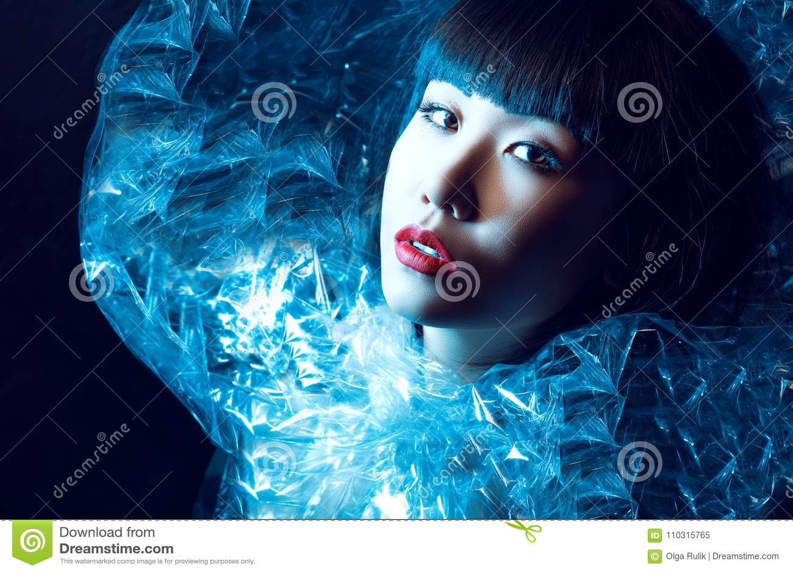 Den ursnygga asiatiska modellen med härligt smink och moderiktig frisyr med frans som bär den utsmyckade glänsande iskalla ställn