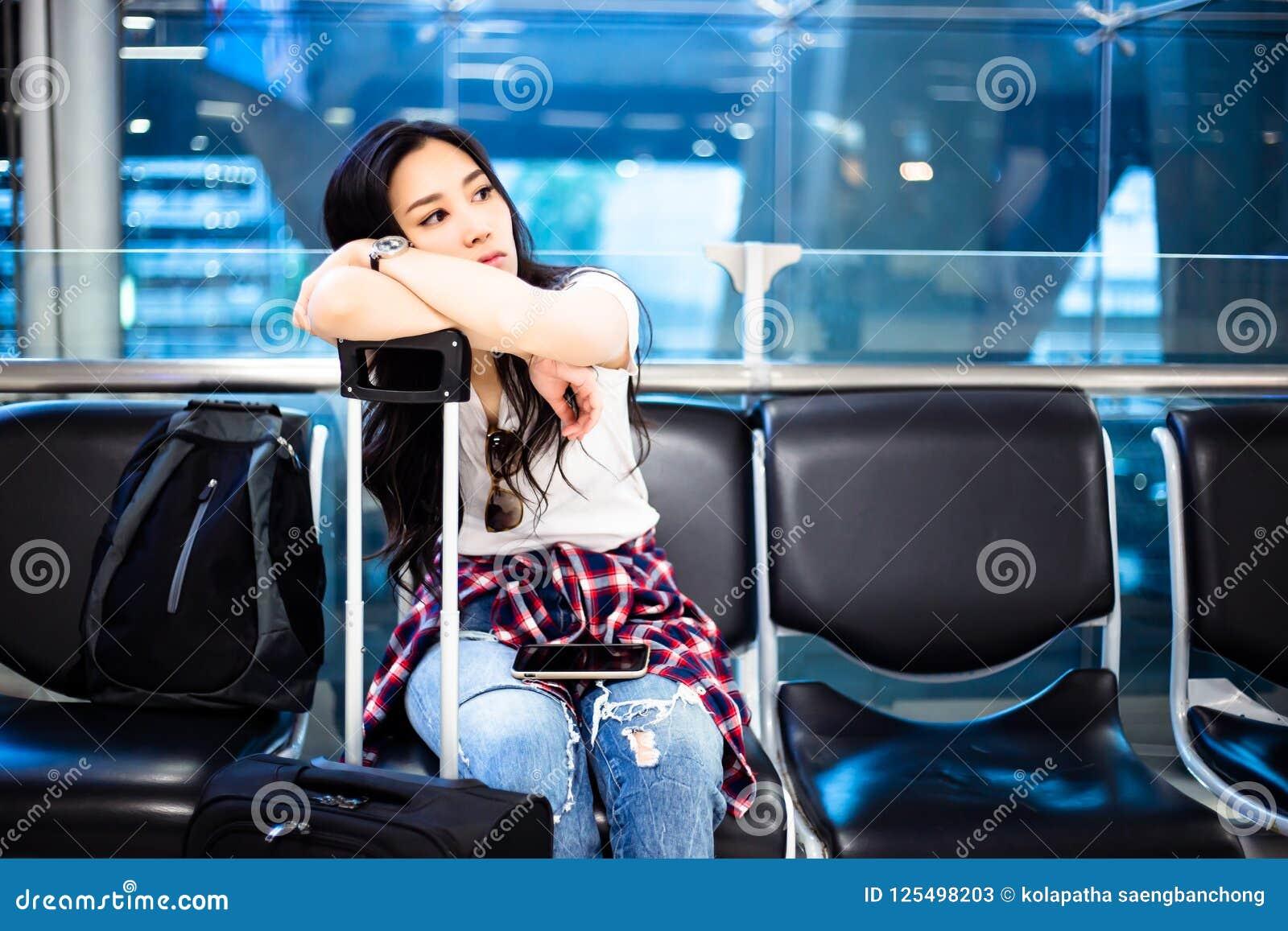 Den ursnygga handelsresandeflickan sitter på en stol på flygplatsen härlig woma