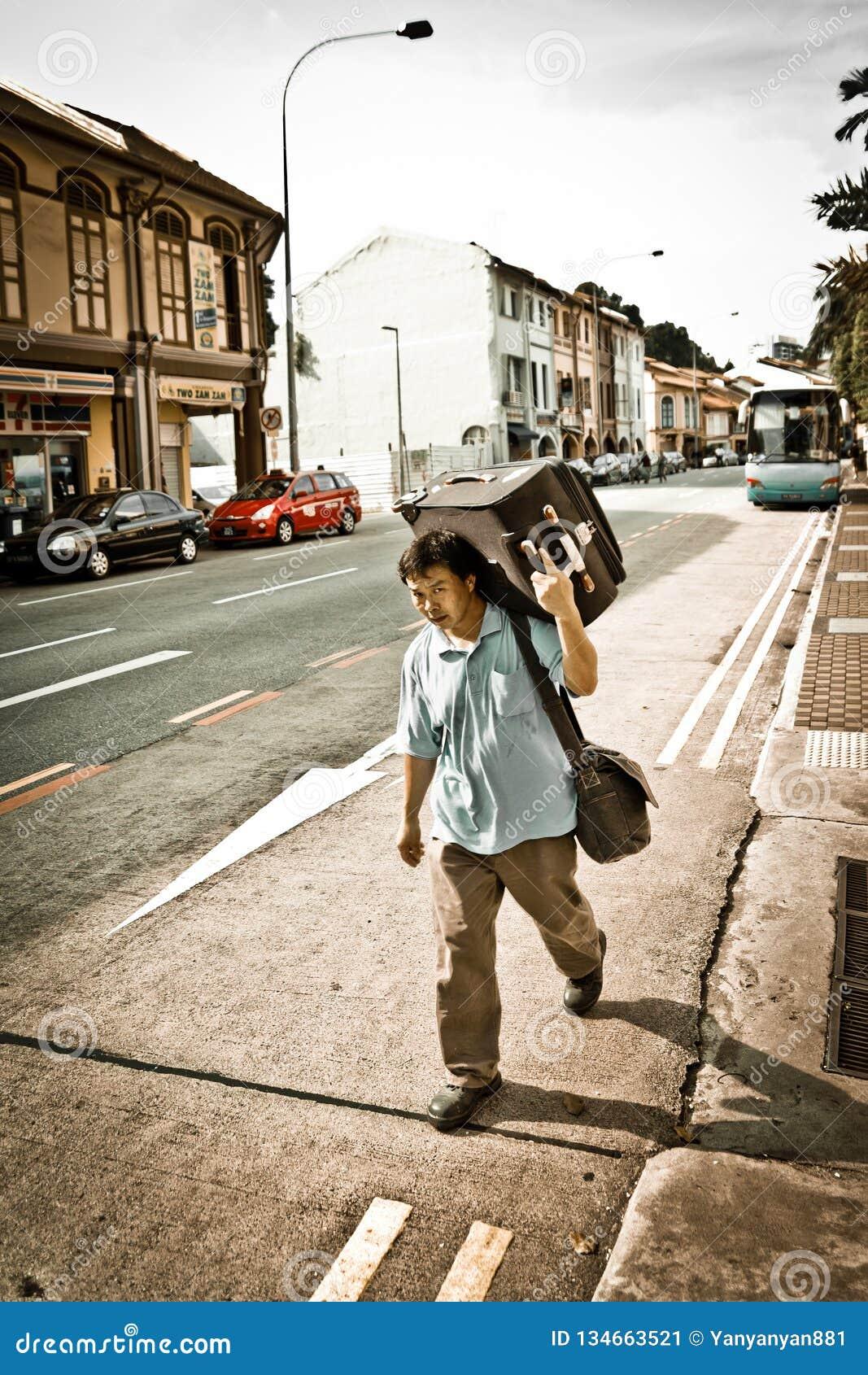 Den utländska kinesiska mannen bär ett stort bagage på vägen längs gatan av Singapore
