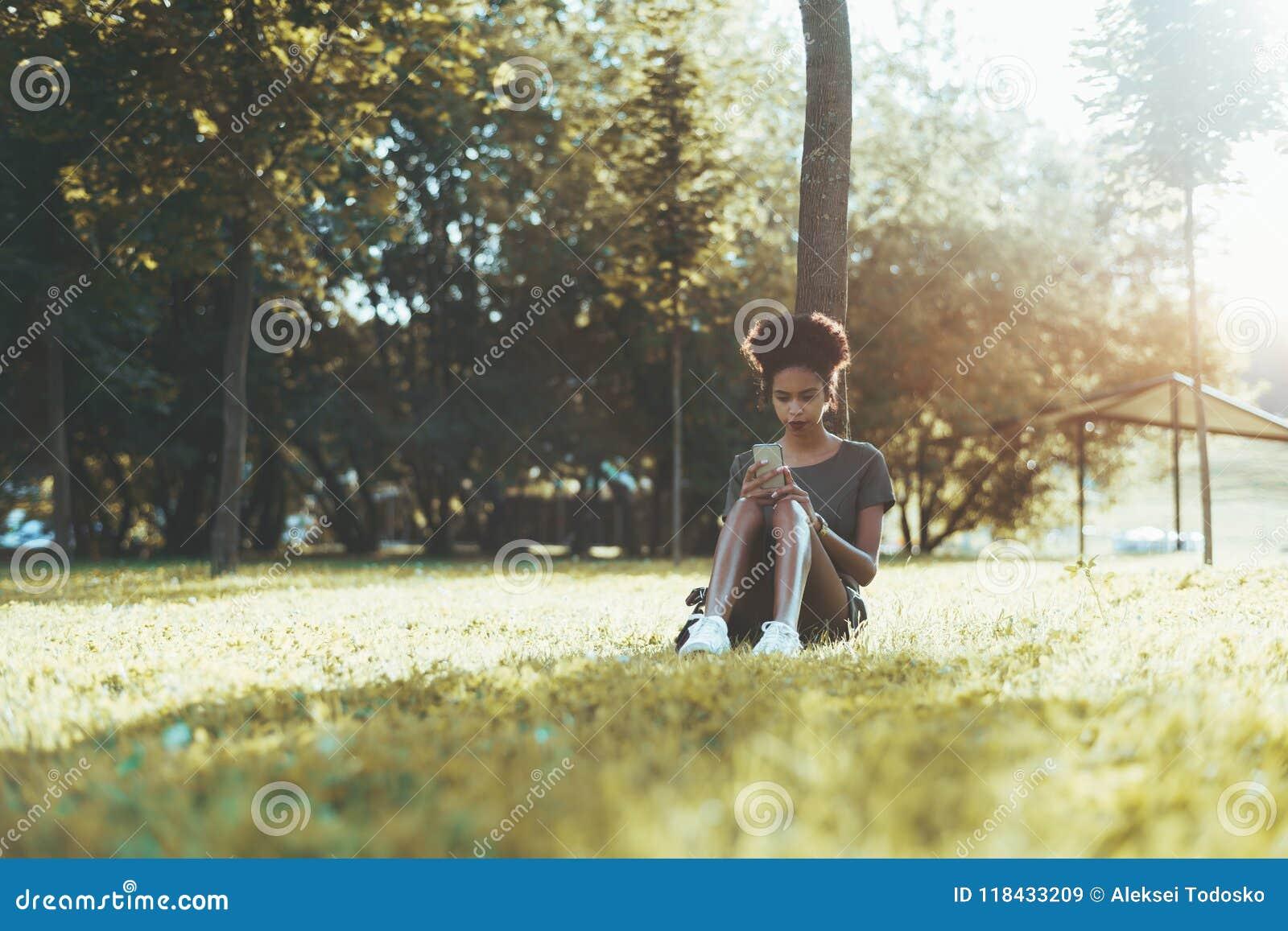 Den utomhus- afro- flickan parkerar in att prata via mobiltelefonen