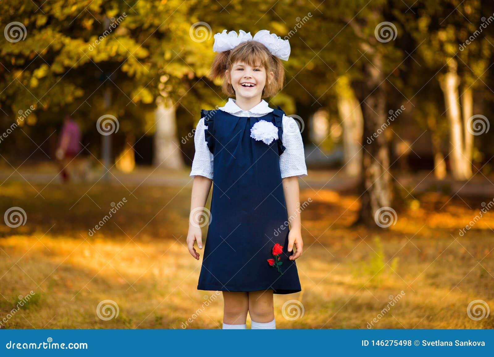 Den utomhus- st?enden av den lyckliga lilla skolflickan i skolalikformig parkerar in