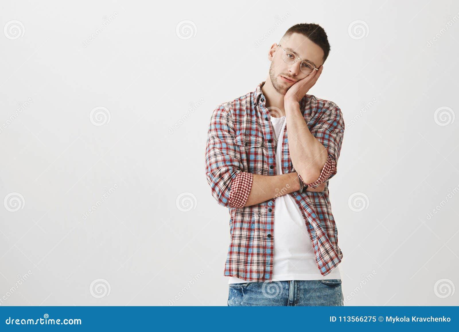 Den uttråkade och utmattade unga stiliga mannen med borstet i stilfulla exponeringsglas som lutar huvudet gömma i handflatan på,