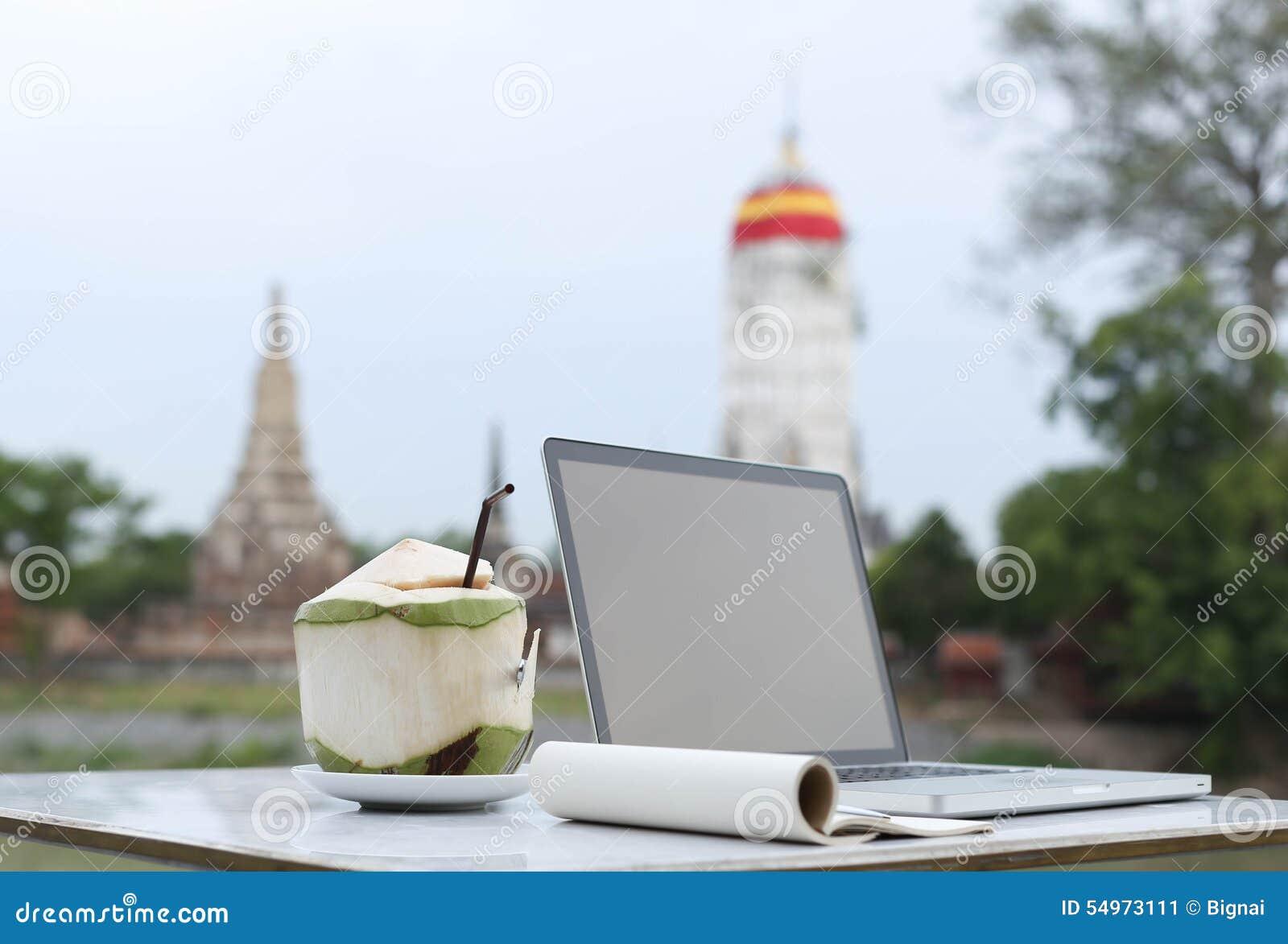 Den utvalda fokusen och kokosnöten dricker med den tomma notepaden