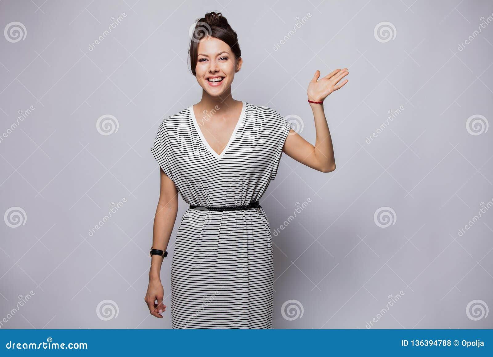 Den vänliga kvinnan säger högt till nya grannar Stående av den charmiga unga känslobetonade kvinnan som vinkar med den lyftta han