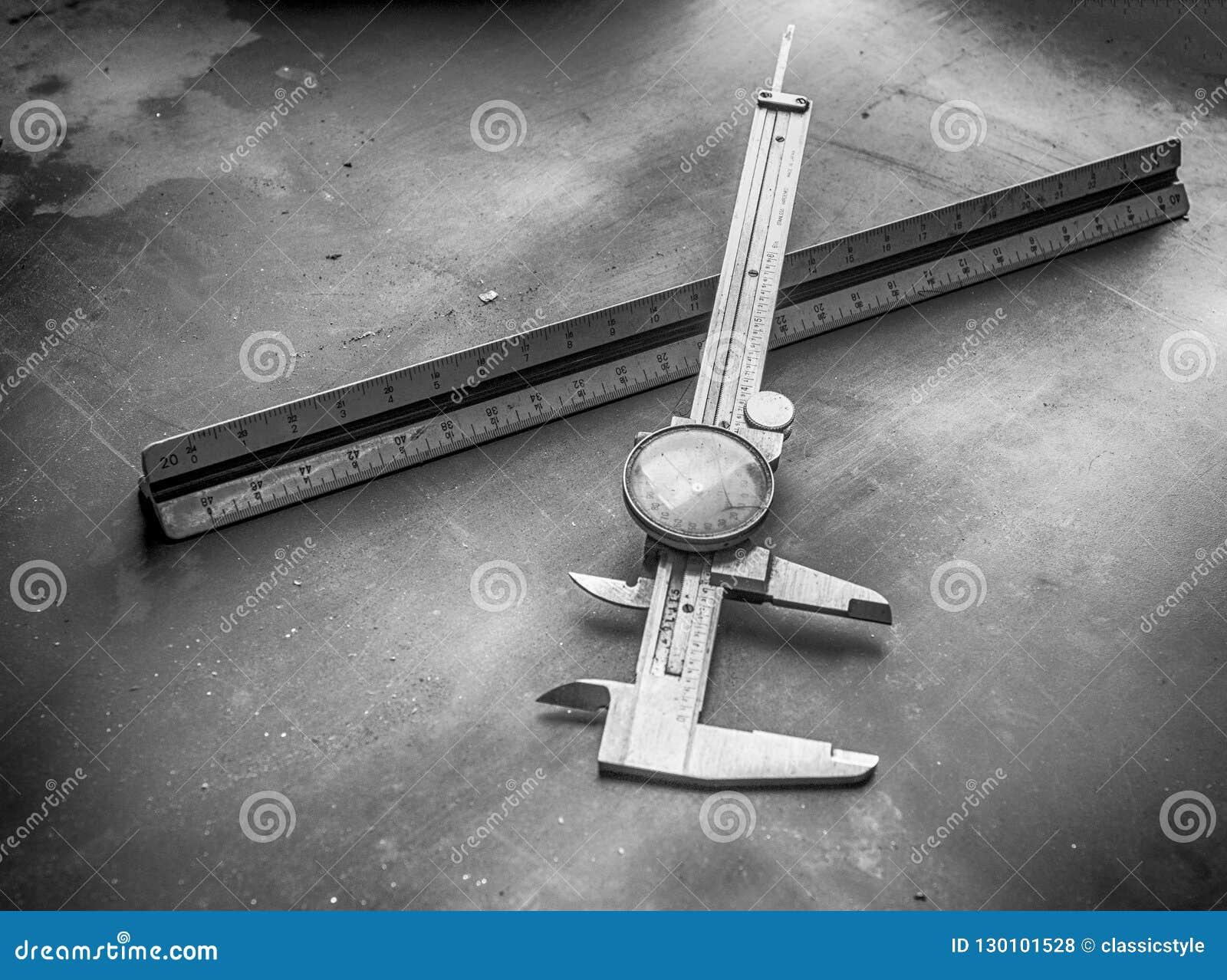 Den visartavlaklämman och linjalen på en maskin shoppar stålbänken