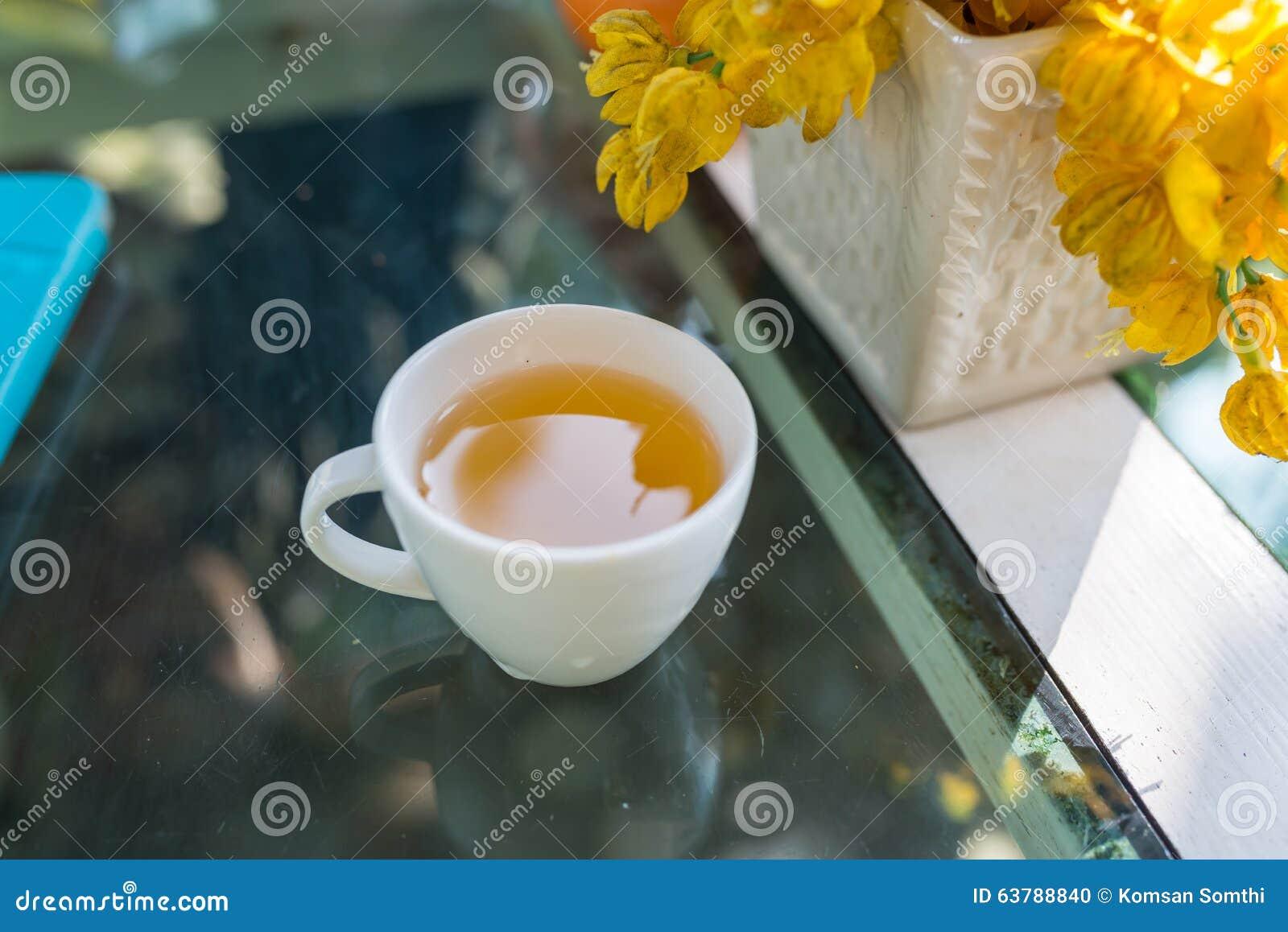 Den vita koppen häller varmt grönt te