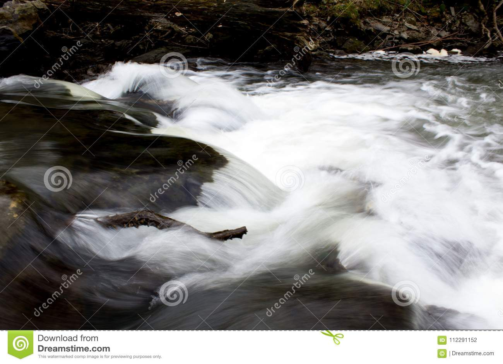 Den vita kristallklara flodströmmen som över rusar, vaggar