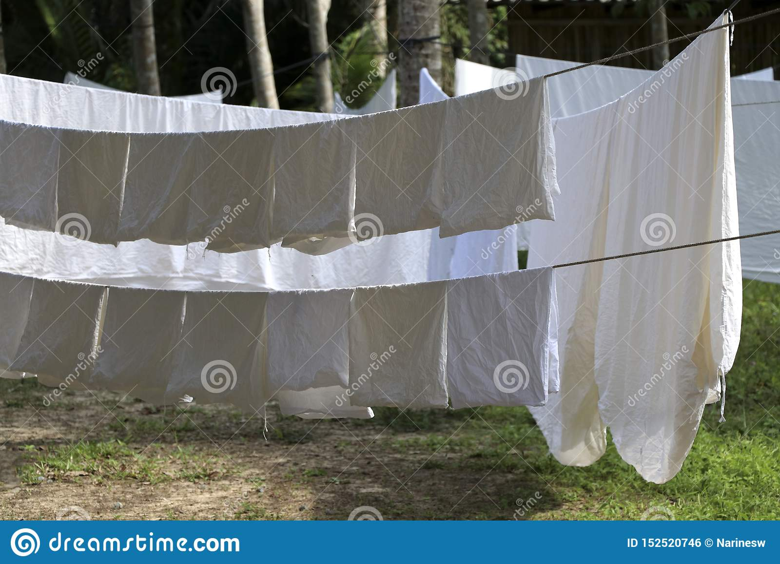 Den vita torkduken exponeras till solen på klädstrecket