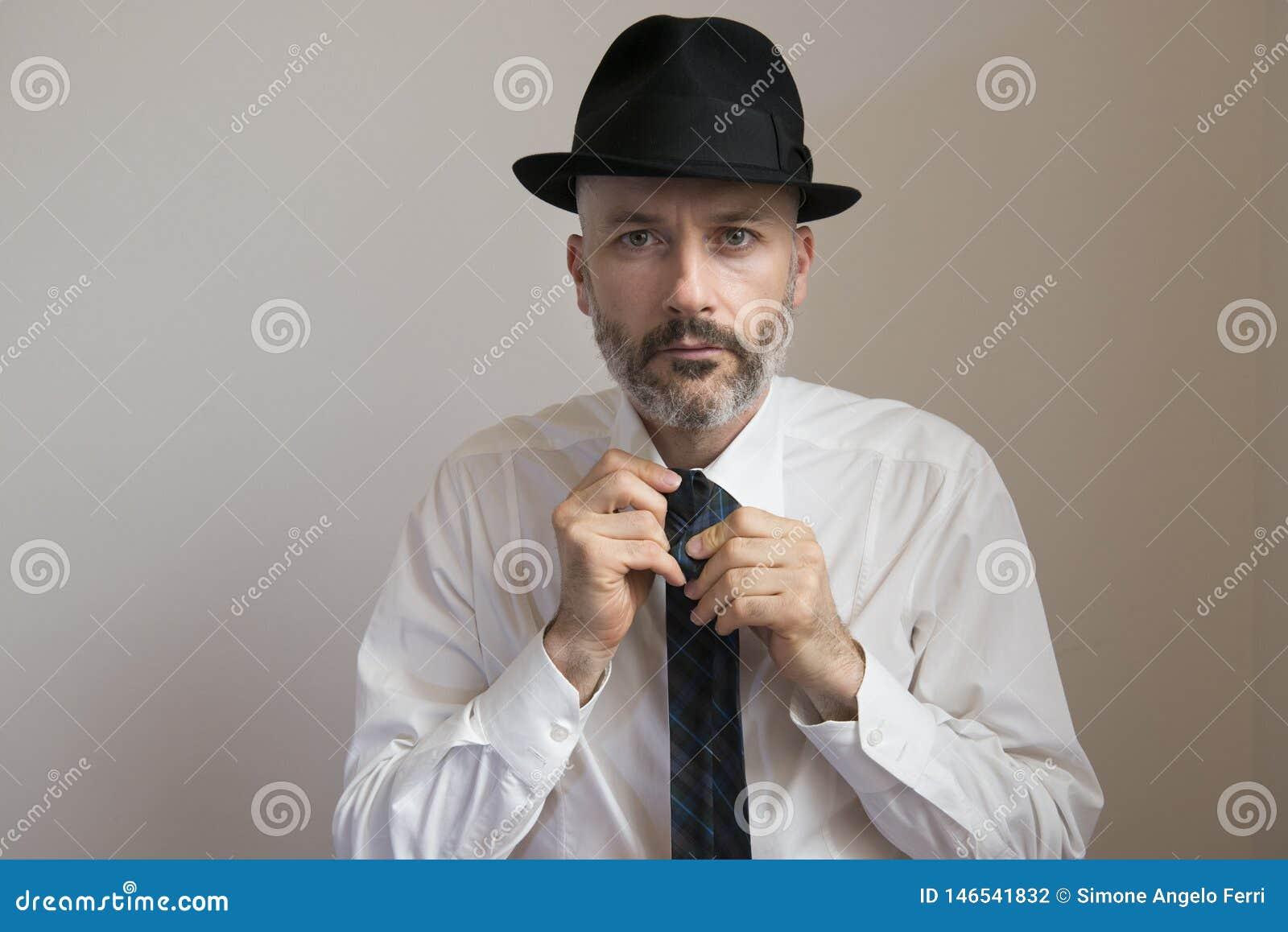 Den vuxna mannen med hatten och skägget knyter hans slips