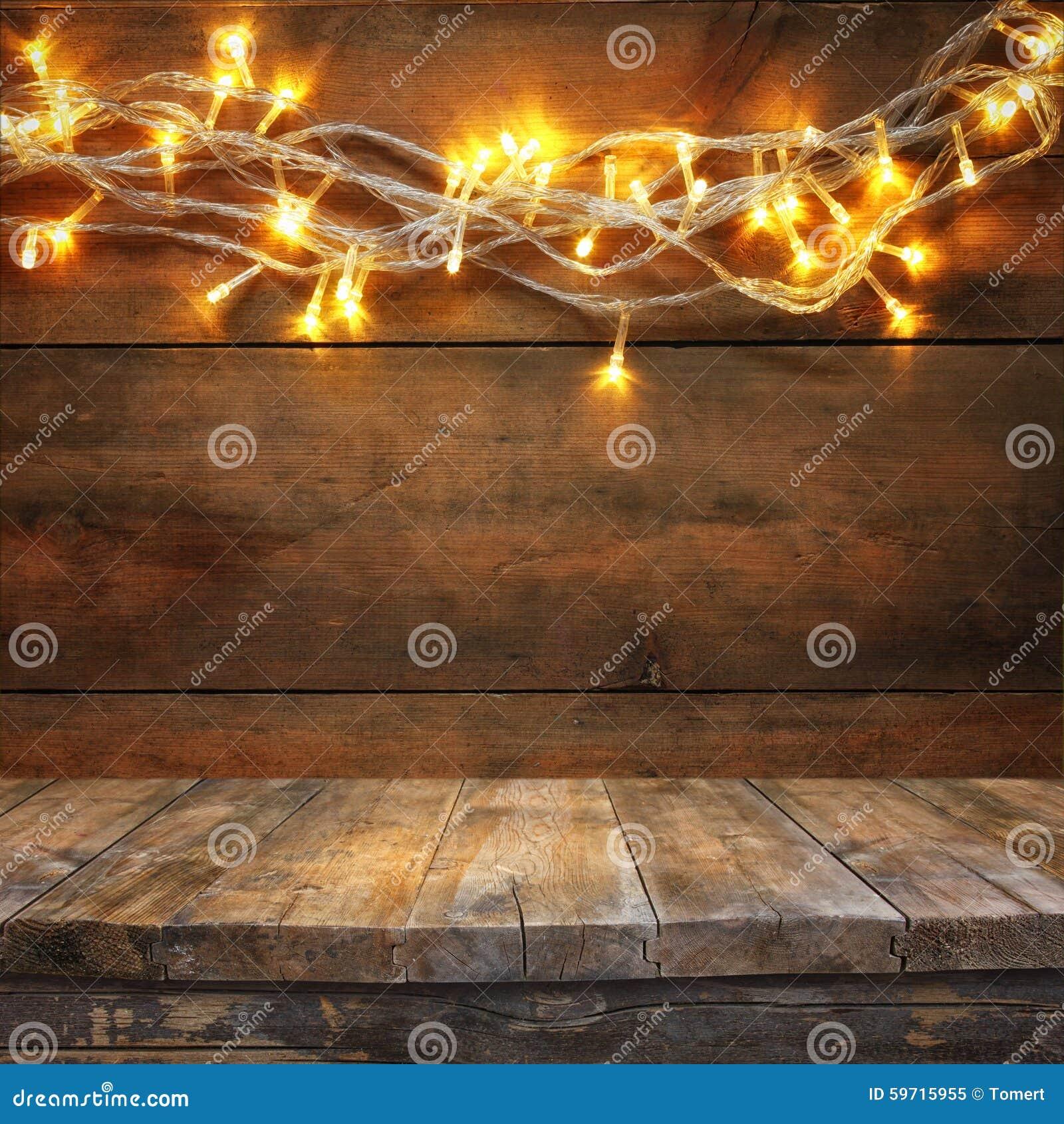 Den Wood brädetabellen av jul värme framme guld- girlandljus på trälantlig bakgrund Filtrerad bild Selektivt fokusera