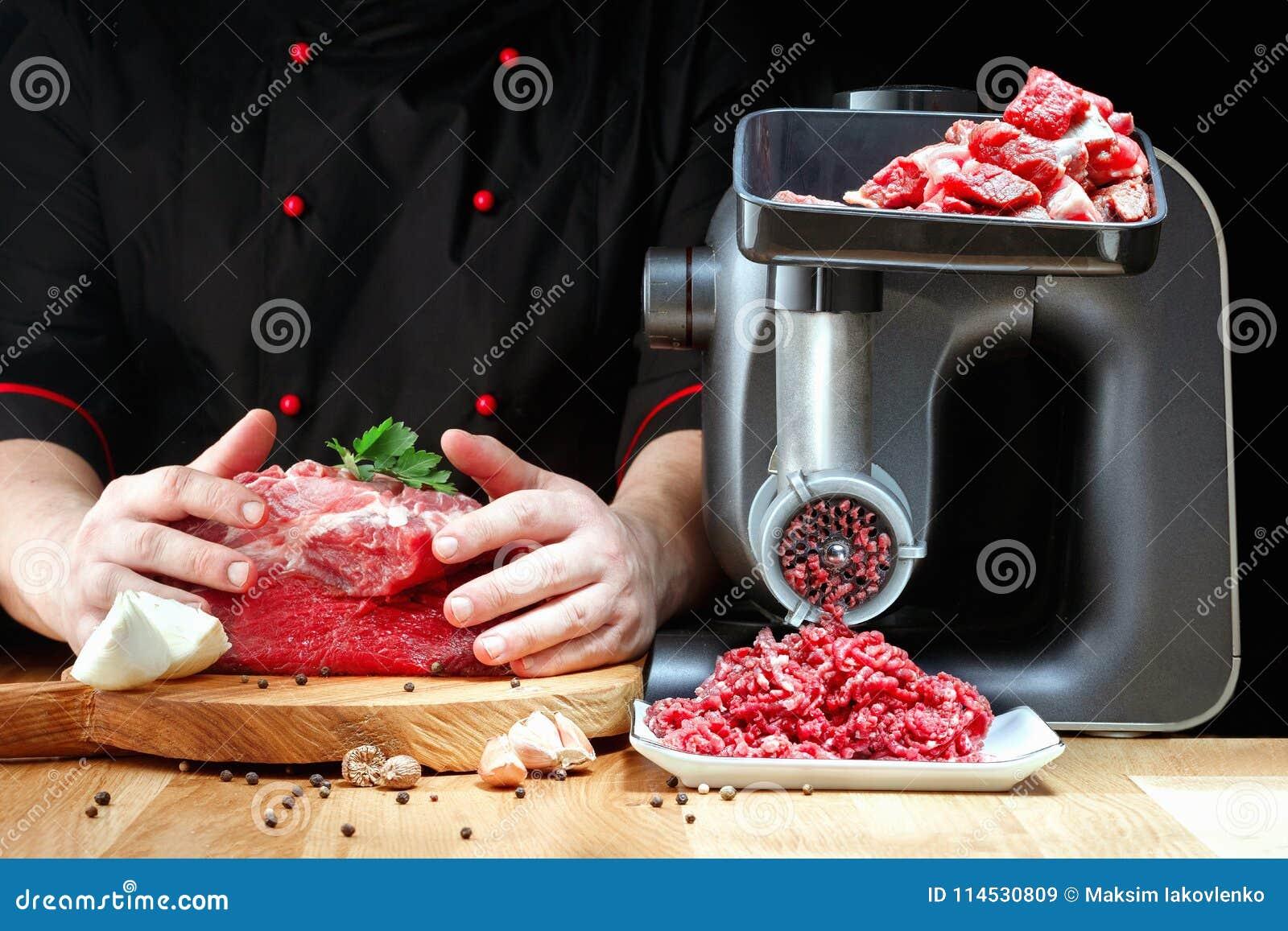 Den yrkesmässiga kocken förbereder köttfärs från nytt kött på mörk bakgrund