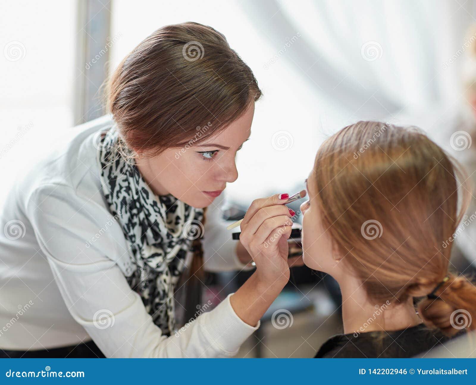Den yrkesmässiga makeupkonstnären gör smink i en skönhetsalong
