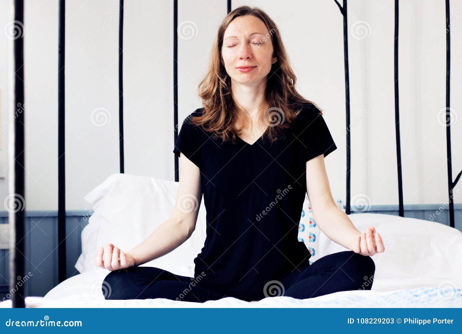 Den Zen Business kvinnan som gör yogameditation på säng, kopplade av i lotusblomma poserar