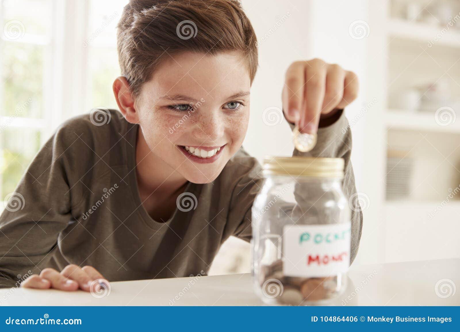 Denaro per piccole spese di risparmio del ragazzo in barattolo di vetro a casa