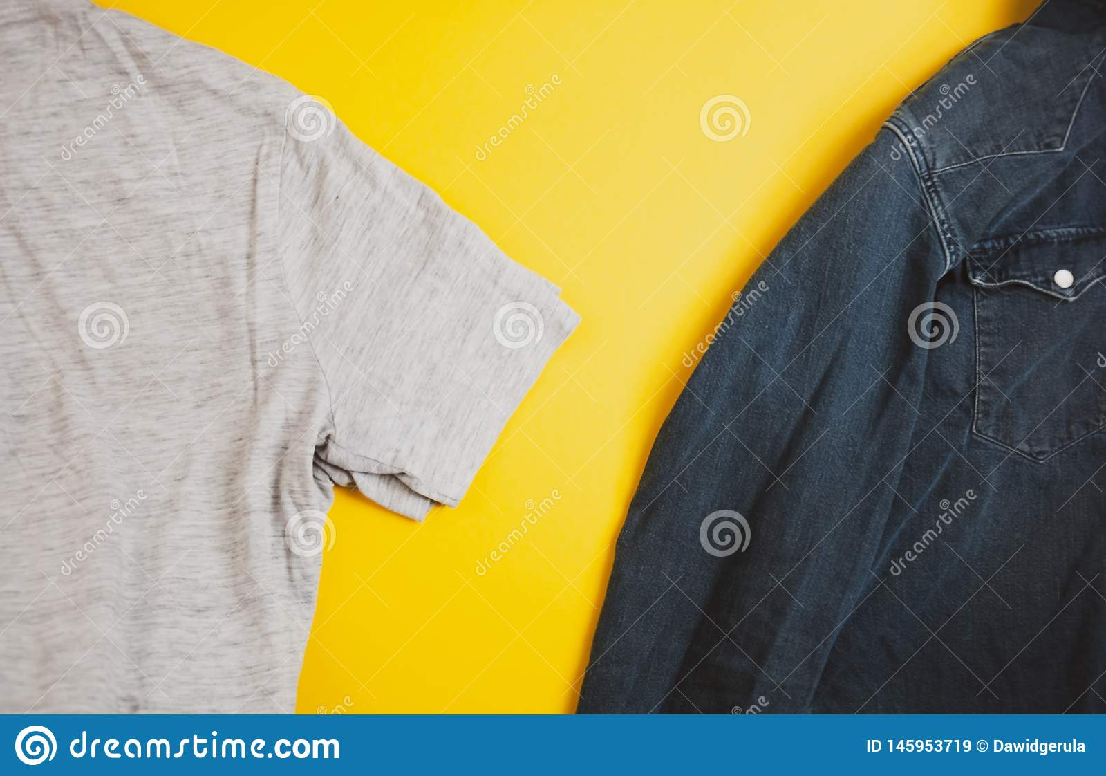 Denim jacket and grey tshirt on two sides of the photo, on yellow background, with copyspace