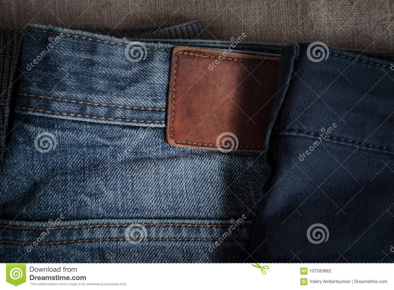 denim pants of different colors lie on old linen burlap abstract background